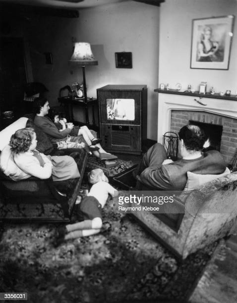 A British family watching television in their lounge Original Publication Picture Post 7077 Colour TV When And How pub 1954