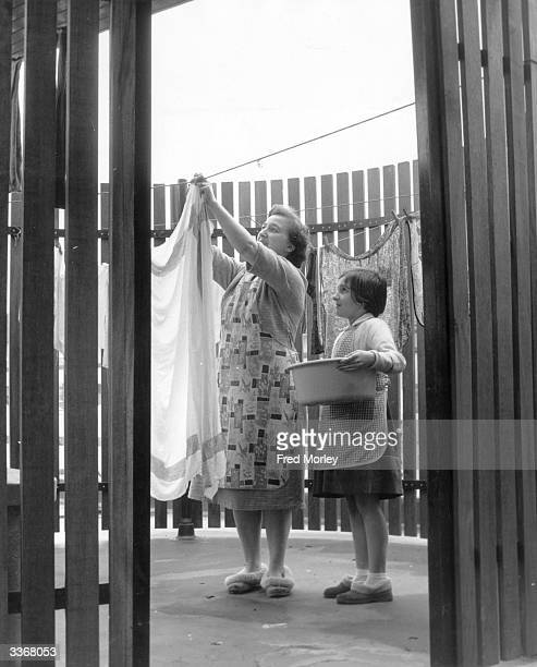 Mrs Clemo's nine year old daughter helps her to hang out the washing in their new drying porch which although outside is shielded from the elements...