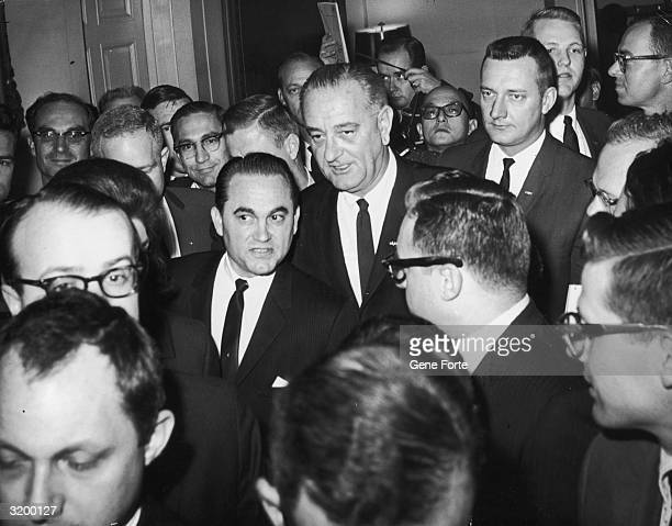 Alabama Governor George Wallace and US President Lyndon B Johnson are surrounded by reporters as they leave their 3 hour meeting Washington DC