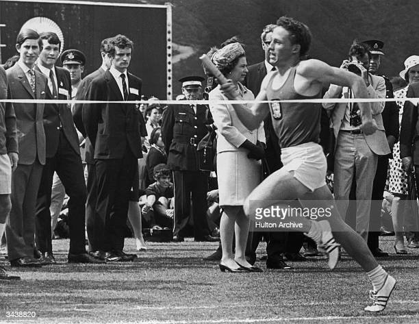 Queen Elizabeth II and Prince Charles watching the climax of a relay race during a secondary school sports day at Hutt Recreation Ground in New...