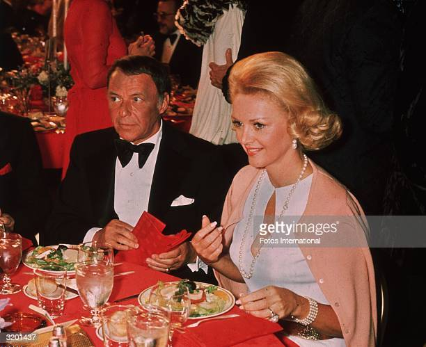 American actor and singer Frank Sinatra sitting at a dinner table next to his fiancee showgirl Barbara Marx at the American Film Institute Tribute to...