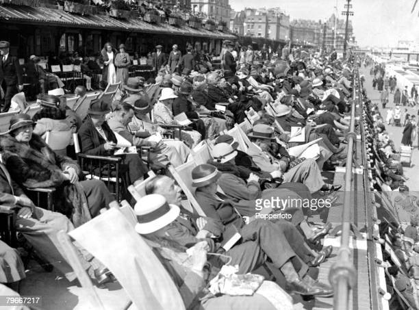 13th May 1934 Seaside Holidays in Britain Crowds of peop e relaxing in their deck chairs as they Enjoy the sunshine on Eastbournes Promenade England