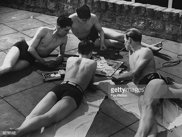 Group of sunbathers, having a smoke and playing a game of monopoly at an open air pool.