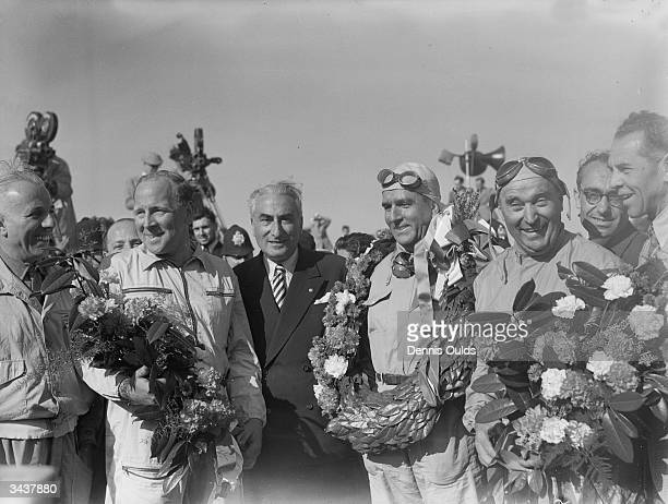 British racing driver Reg Parnell , Italian driver Giuseppe Farina and Italian C Fagioli, members of the victorious Alfa Romeo team at the finish of...