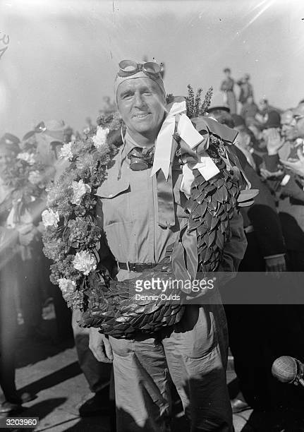 Italian Alfa Romeo racing driver Giuseppe Farina, garlanded after his triumph at Silverstone.