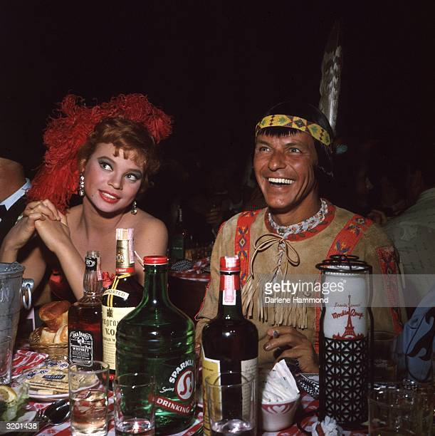 American actor and singer Frank Sinatra sits behind liquor bottles next to his girlfriend actor Juliet Prowse at a SHARE Boomtown benefit party at...