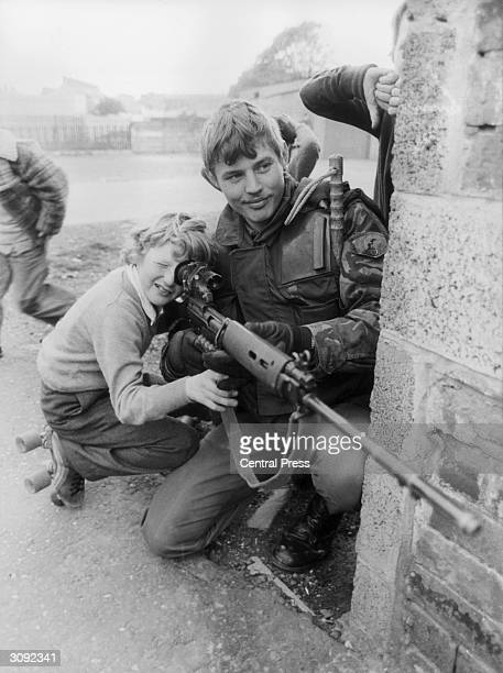A British soldier lets a young boy look through the sights of his rifle in Belfast