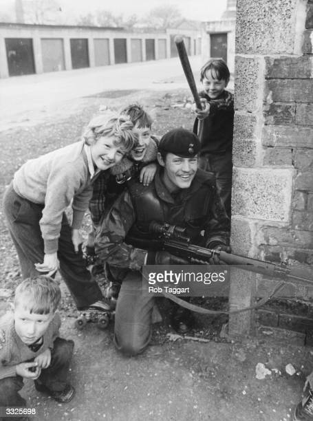 Schoolboys in a Catholic area of Belfast at play on the streets near a British soldier on patrol