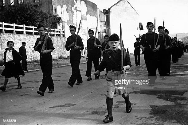 Youth parade of Spanish schoolchildren makes its way along the road wearing the black shirts of the Fascists and carrying dummy rifles. Their home of...