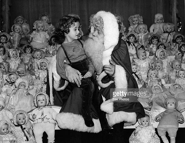 A vast number of dolls surrounds Father Christmas as he talks to a girl sitting on his knee