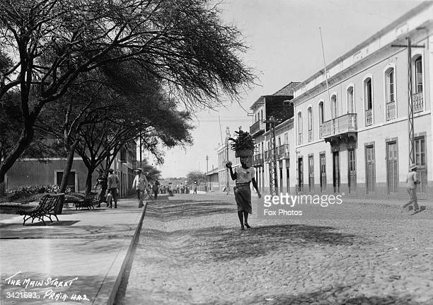 Awoman balances a basket of firewood on her head as she walks down the main street of Porto Praia Sao Tiago Cape Verde islands