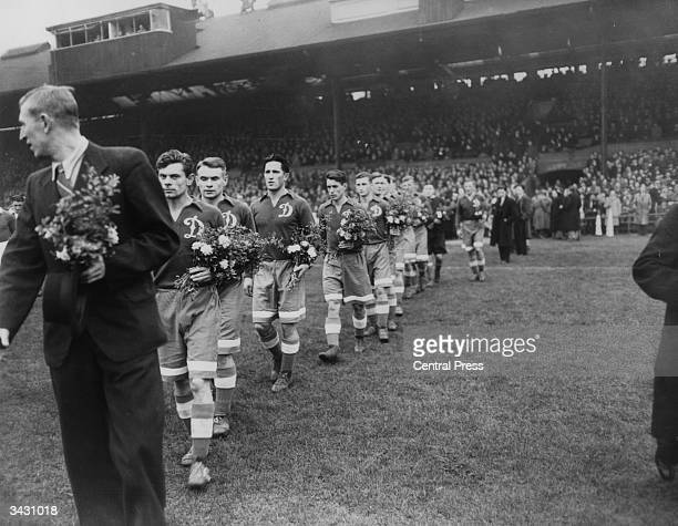 Members of the Russian football team Dynamo Moscow walk out onto the pitch at Stamford Bridge London carrying bouquets for their Chelsea opponents It...