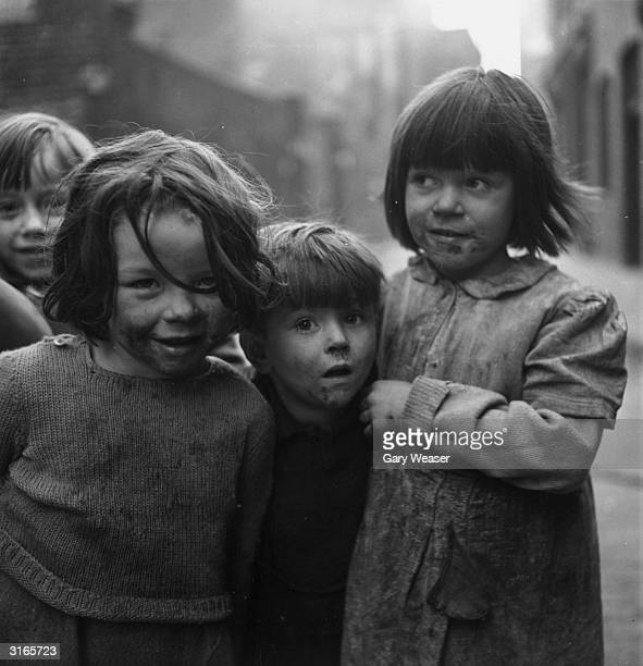 Dirty faced and dressed in dirty clothes three young children from Cable Street Stepney in the east end of London show an interest in the camera