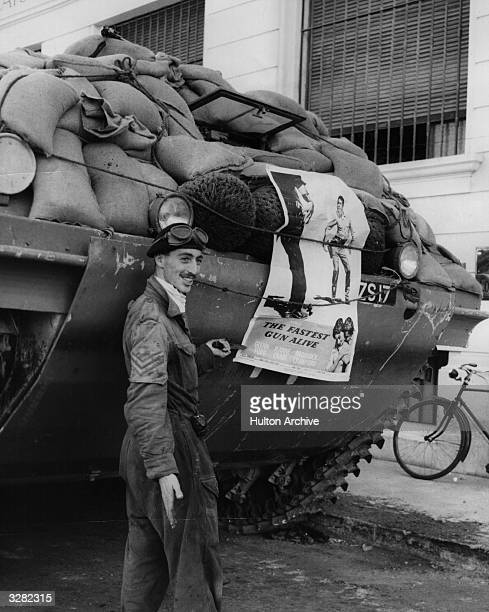 A British tank driver in Port Said during the Suez conflict beside his tank to which he has attached a poster for the US film 'The Fastest Gun Alive'