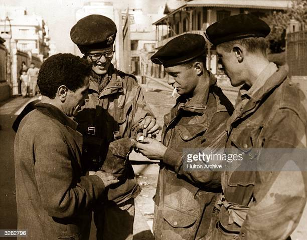 Soldiers examining a watch from a street vendor in Port Said during the Suez Crisis.
