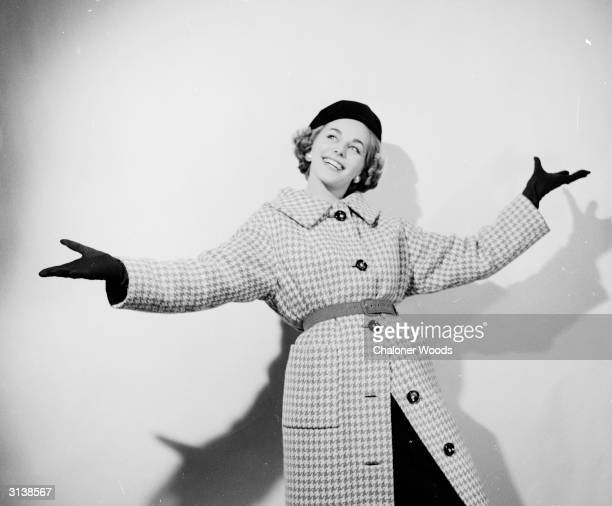 A woman throws out her arms to demonstrate the abundance of space that allows her to show off her fashionable new winter overcoat