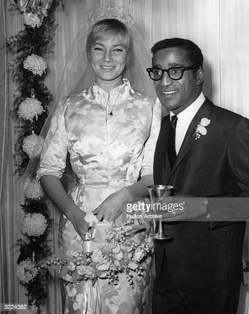 American actor, singer and dancer Sammy Davis Jr. Stands next to his wife, Swedish actor May Britt, at their wedding reception at Davis's home,...