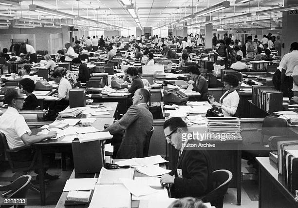 View of a long office with male and female employees sitting at their desks working with stacks of papers at Rocketdyne a division of North American...