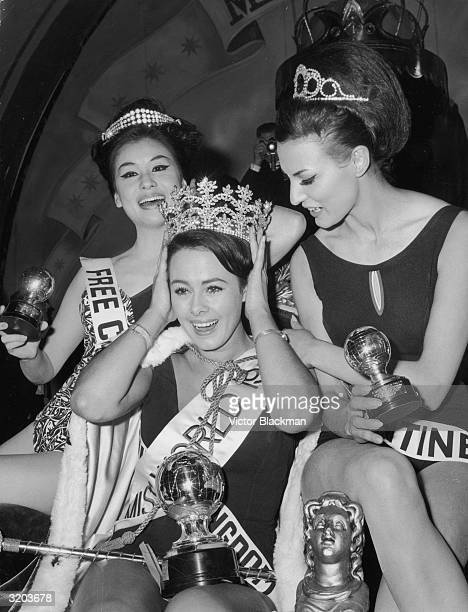 The winner of the Miss World beauty pageant, Ann Sidney , Miss United Kingdom, holds her hands to her crown while runners-up, Linda Lin , Miss Free...