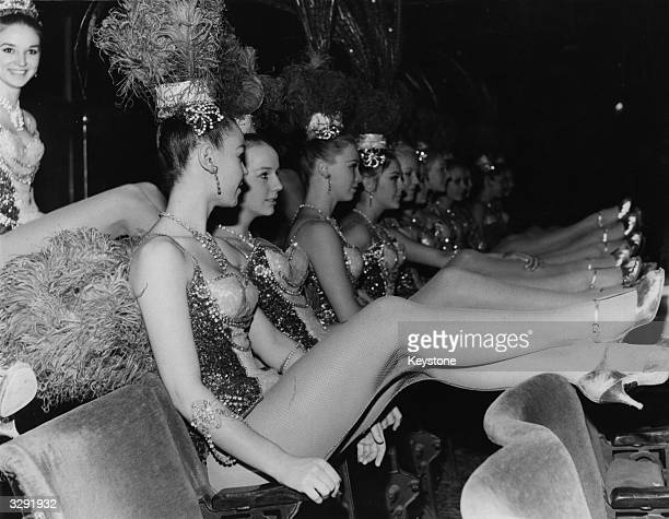 The long-legged Bluebell Girls, stars of the Royal Variety Performance at London's Palladium Theatre, relax in the stalls during rehearsals.