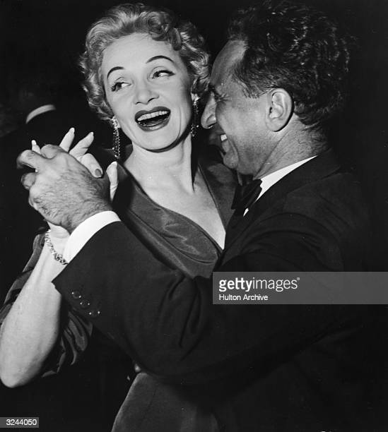 German actor Marlene Dietrich laughs as she dances with Turkishborn film director Elia Kazan at the afterpremiere party for director George Cukor's...