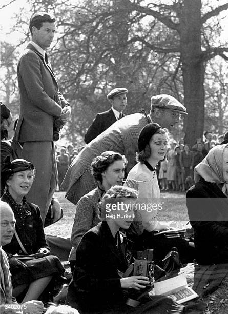 Queen Elizabeth II holding a camera at the Olympic Horse Trials at Badminton whilst Princess Margaret sits behind her smoking a cigarette and...