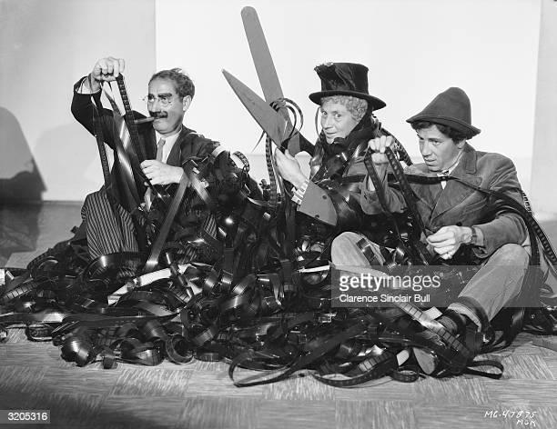 The Marx Brothers Groucho Harpo and Chico cut to pieces a large pile of film footage with an outsize pair of scissors