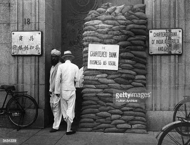 Business as usual despite sandbags in the doorway at the Chartered Bank of India Australia and China in Shanghai during the SinoJapanese conflict