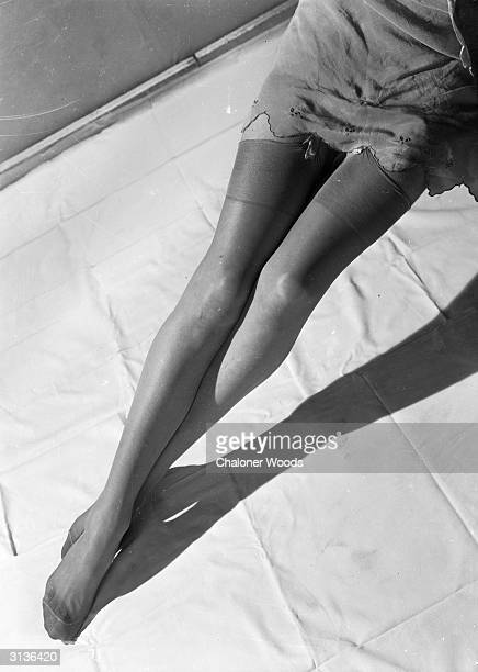 A pair of woman's legs clad in silk stockings secured by suspenders