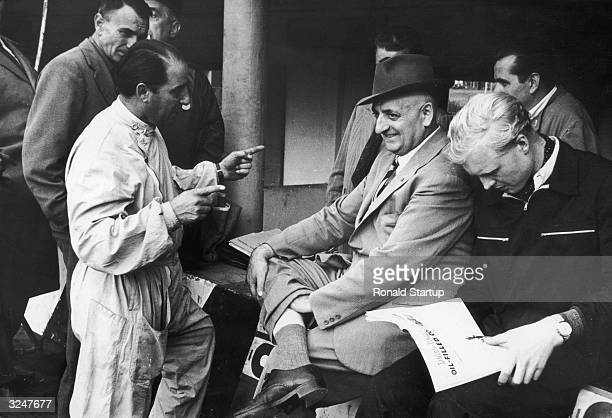 Italian racing driver and sports car manufacturer Enzo Ferrari in the Ferrari pit at Monza with Italian racing driver Alberto Ascari and British...