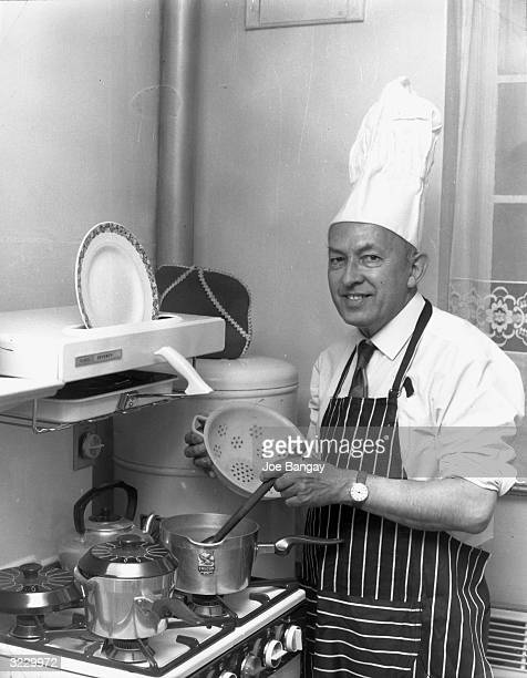 British senior George Waller smiles while stirring a pot on the kitchen stove, at home in London. He wears a chef's hat and a striped apron. Waller...
