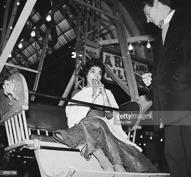 American singer Eartha Kitt eating an apple as she is joined by her companion on a fairground ride during a visit to the UK