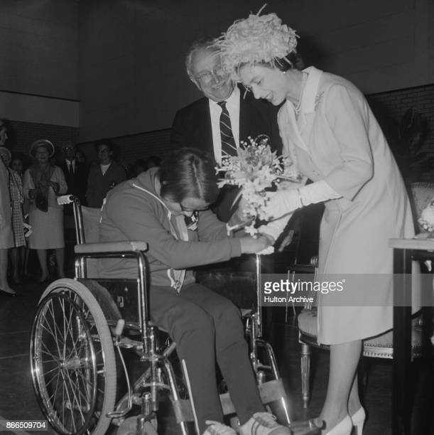 13yearold Bente Gronli bows as she presents a bouquet to Queen Elizabeth II in occasion of the opening of the Stoke Mandeville Stadium where the...