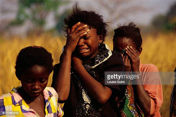 A 13yearold girl mourns the death of her mother with her two young cousins already orphans themselves Seventy percent of the world's HIV/AIDS victims...