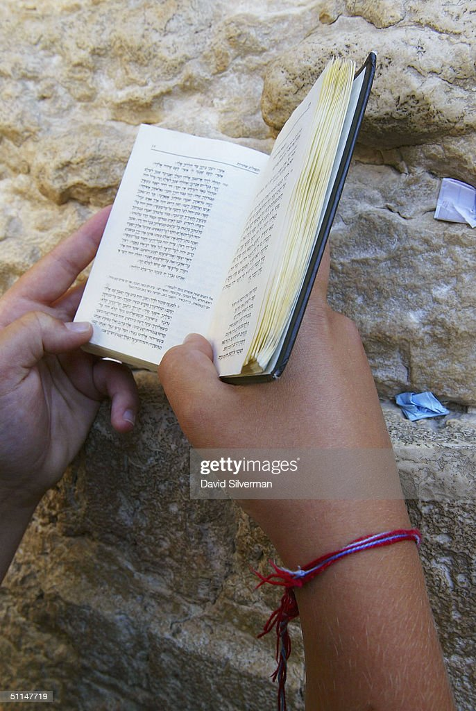 Jewish youth Yehuda Holzer, 13, from Long Island, New York, wears his Kabbalah (Jewish mysticism) Red String Bracelet while praying at the Western Wall, Judaism's holiest site, August 6, 2004, in Jerusalem's Old City, Israel. American singer Madonna, who is reported to be planning a Kabbalah-linked visit to Israel in September, has become known for wearing the bracelets since she delved into the ancient Jewish practise some six years ago.