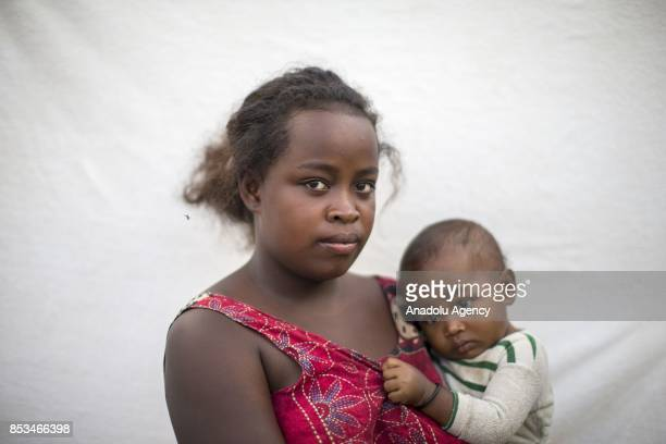 13yearold Sandra Mahafaly holding her son in her arms poses in Antananarivo Madagascar on September 24 2017 In Madagascar most of the girls with no...