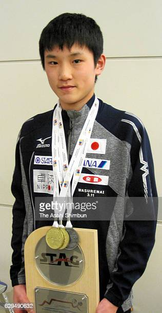 13yearold table tennis player Tomokazu Harimoto poses for photographs with his medals and shield on arrival at Haneda International Airport on...