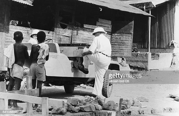 *14011875Arzt Theologebesteigt seinen Jeep in Lambarene