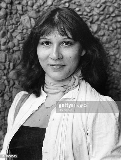 Schauspielerin Dsitzt auf einem Stuhl an eine Mauergelehnt1975