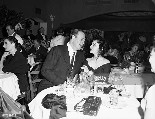 Actor John Wayne and his wife Pilar dine at the El Morocco Club