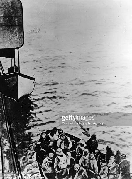 Survivors of the 'Titanic' disaster nearing the 'Carpathia', in a lifeboat. The arrow points to Joseph Bruce Ismay, chairman of the White Star Line.