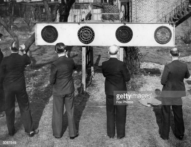 Four men play simultaneous dart games on boards set up in the garden of a house in Clapham, South London. The game was clearly increasing in...