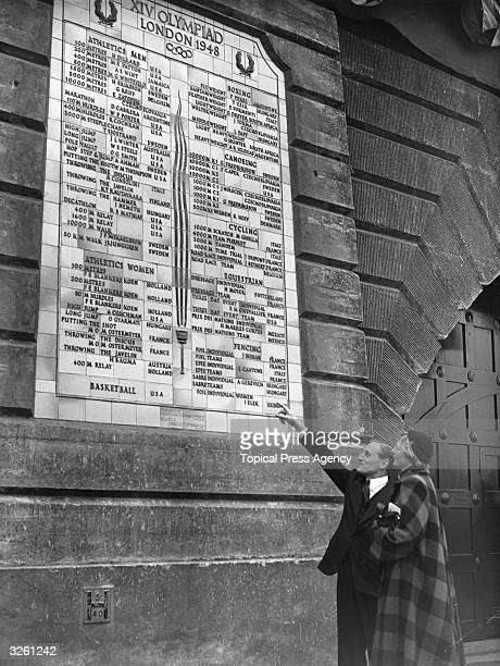Lord Burghley, chairman of the Olympic Games organising committee, pointing out to Fanny Blankers-Koen of Holland, her name on the roll of honour of...