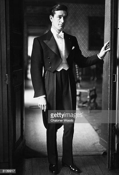 A moody handsome man stands poised in a doorway wearing a white tie and tails the sleeve ends are flared and the jacket has satin lapels and buttons