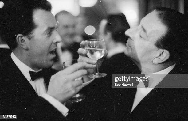 British comedy actor Ronald Shiner drinks a toast with fellow entertainer Brian Rix