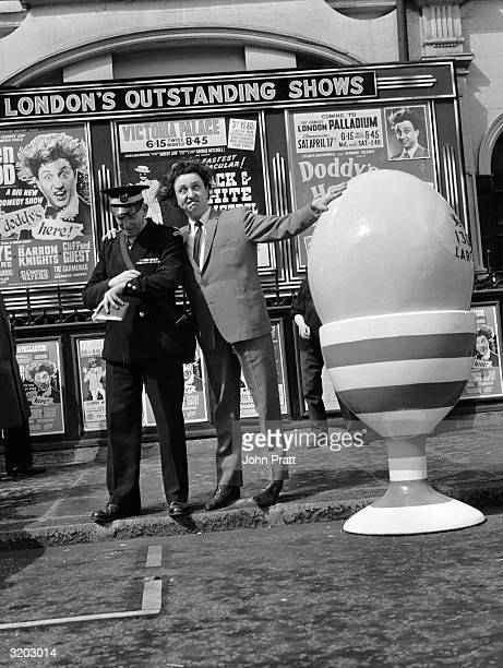 British comedian Ken Dodd outside the London Palladium where the giant egg he is using to promote his Easter show has attracted the attention of a...