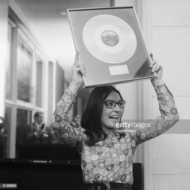 Classically and jazz trained Greek singer Nana Mouskouri who had popular hits and hosted a BBC television series in the 1970's holds up a golden disc...