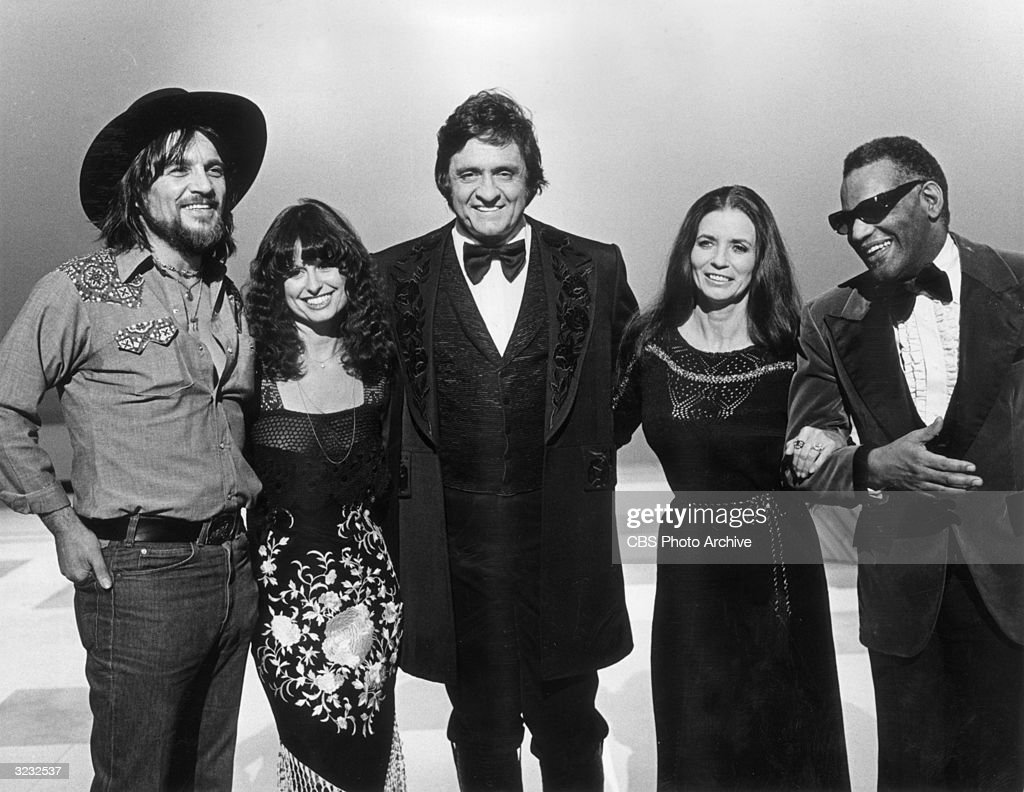 American country singer Johnny Cash (1932 - 2003, center) stands with his guests (left to right) Waylon Jennings (1937 - 2002); Jessi Colter; his wife, June Carter Cash (1929 - 2003); and singer Ray Charles, in a promotional portrait from Cash's television special 'Johnny Cash; Spring Fever'.
