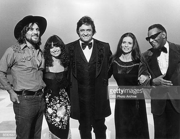American country singer Johnny Cash stands with his guests Waylon Jennings Jessi Colter his wife June Carter Cash and singer Ray Charles in a...