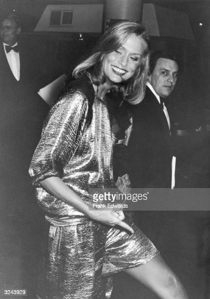 American model and actor Lauren Hutton wearing a short gold lame dress smiles as she walks at the 52nd Annual Academy Awards Dorothy Chandler...